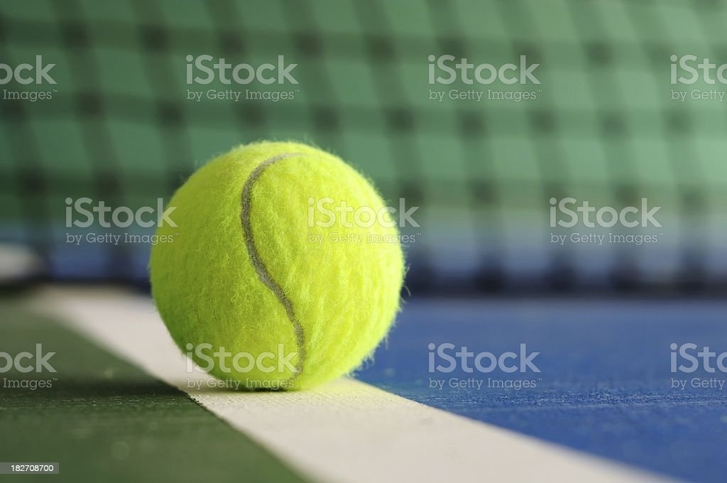 Tennis ball on the line with net in background stock photo