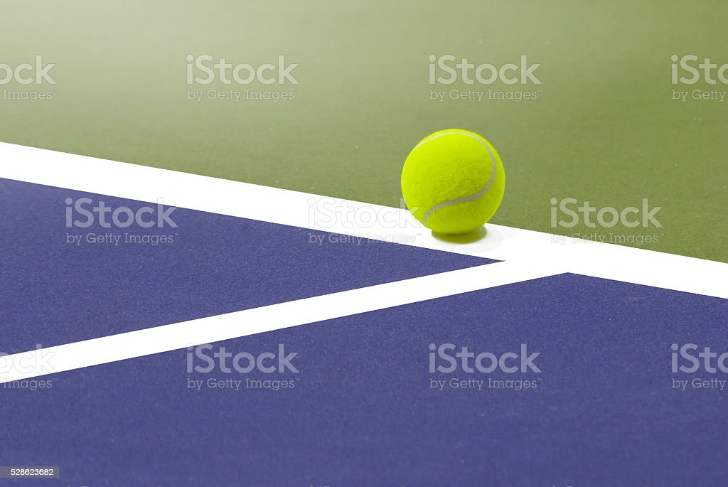 Tennis ball resting on the edge of the field. stock photo