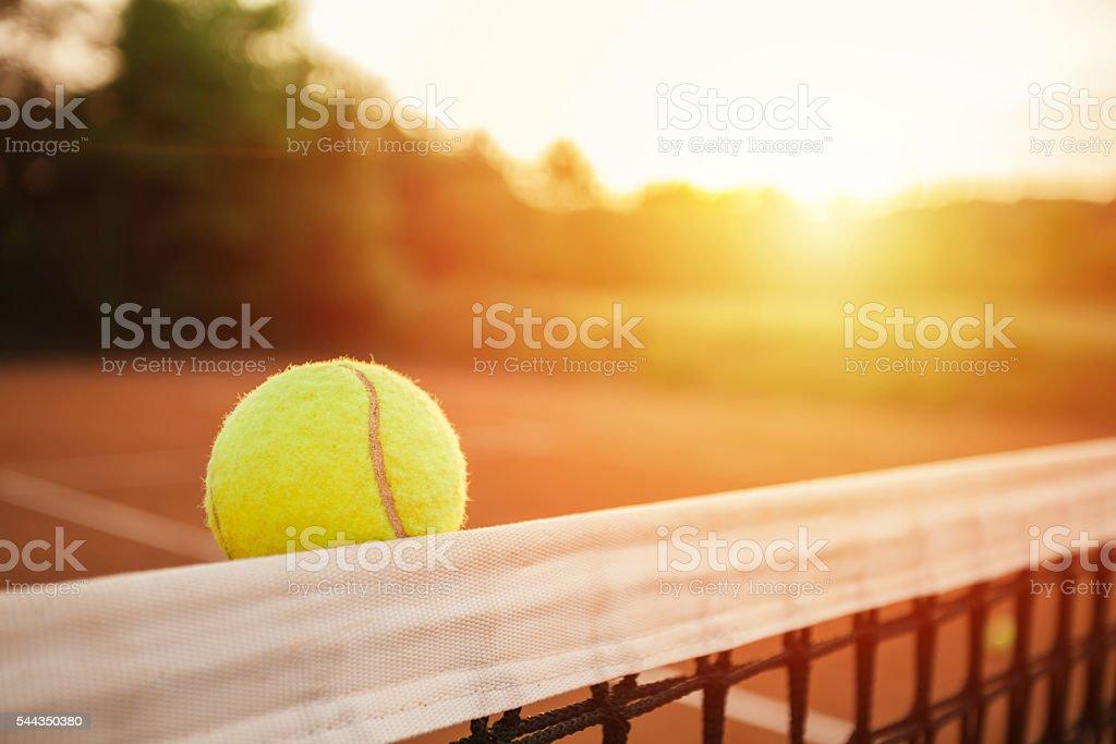 Tennis ball touching the net stock photo
