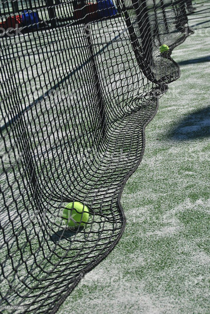 Tennis ball under the net on a tennis paddle court stock photo