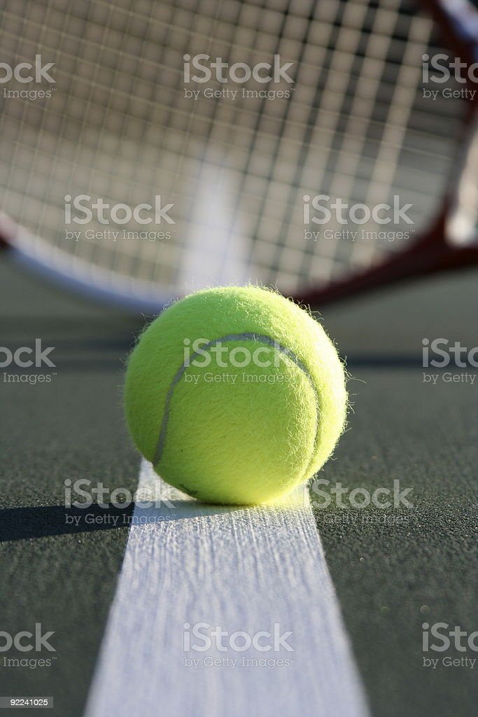 Tennis ball with racket in the background royalty-free stock photo