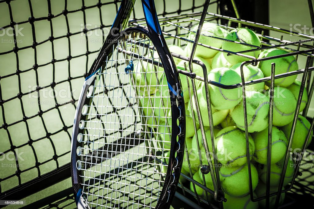 Tennis balls and racquet on court stock photo