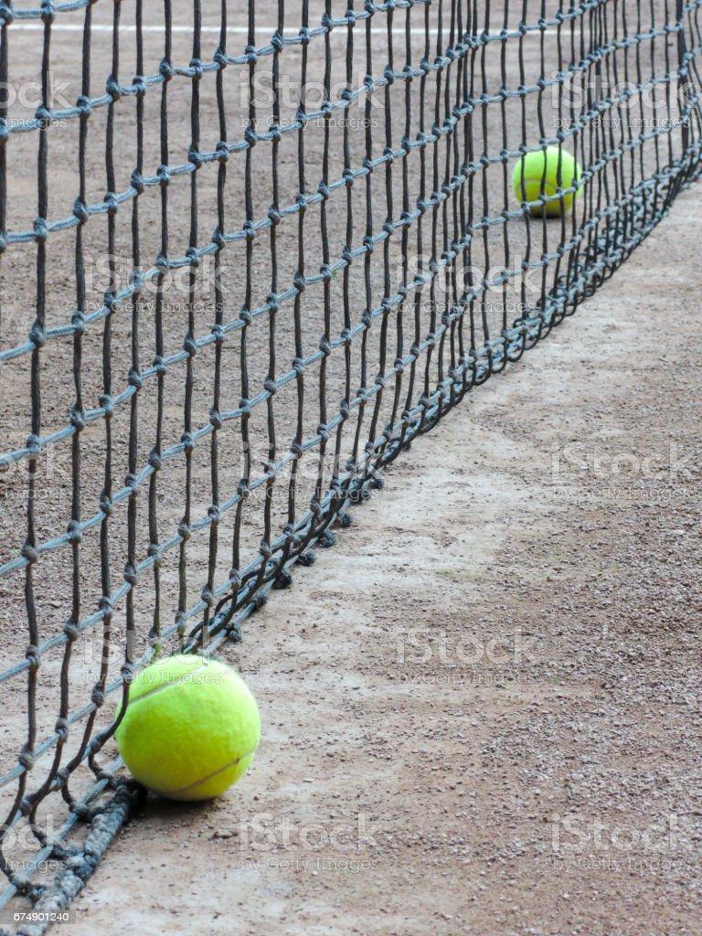 tennis balls near the net on clay court stock photo