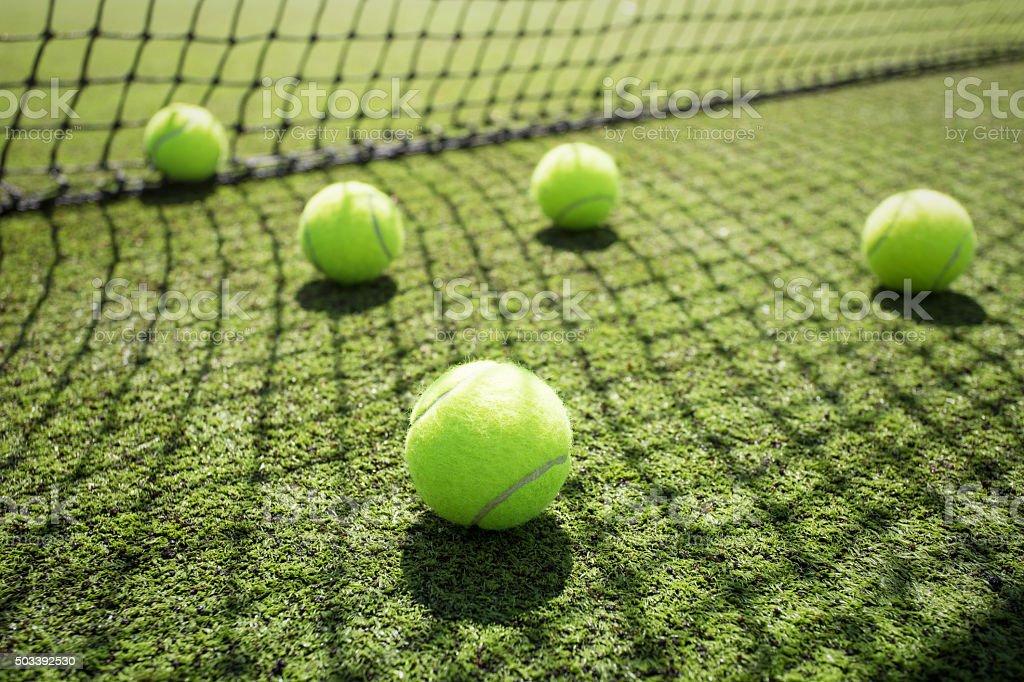 Tennis balls on the court grass stock photo