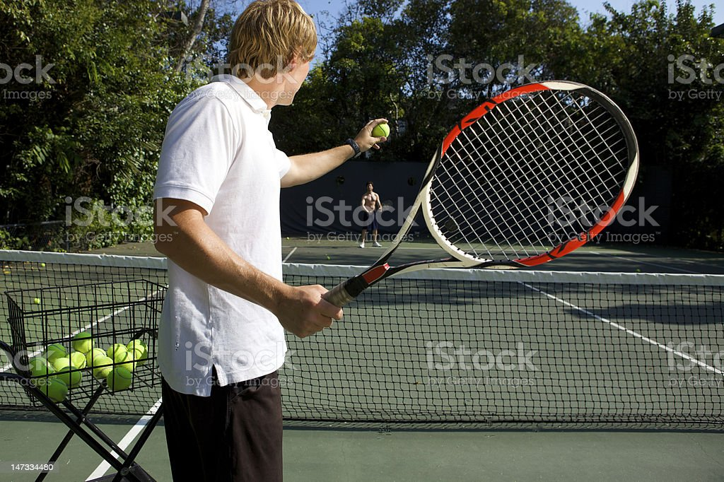 A tennis instructor about to serve a ball to a student  stock photo