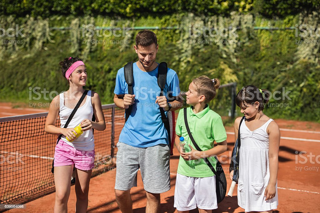 Tennis instructor and group of children talking on tennis court. stock photo