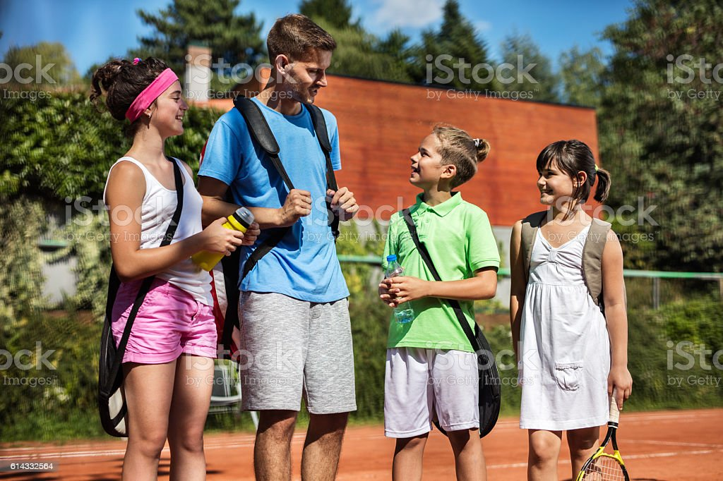 Tennis instructor talking with group of children on tennis court. stock photo