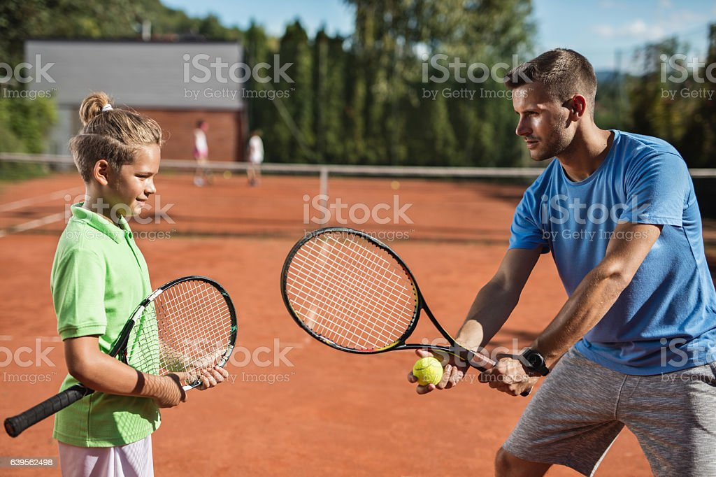Tennis instructor teaching small boy during training class. stock photo