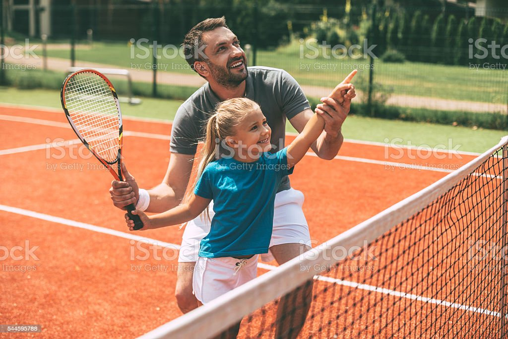 Tennis is fun when father is near. stock photo