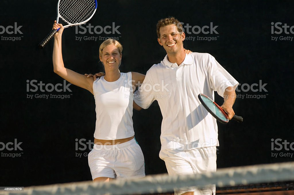Tennis Partners Raising Rackets in Victory stock photo