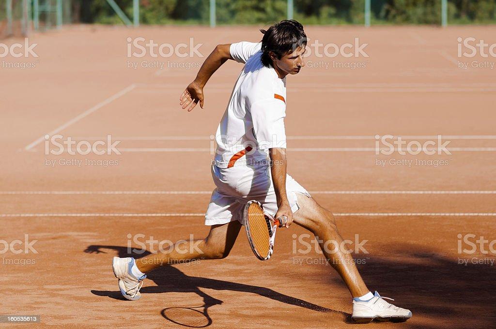 tennis player dashing for ball and sliding stock photo