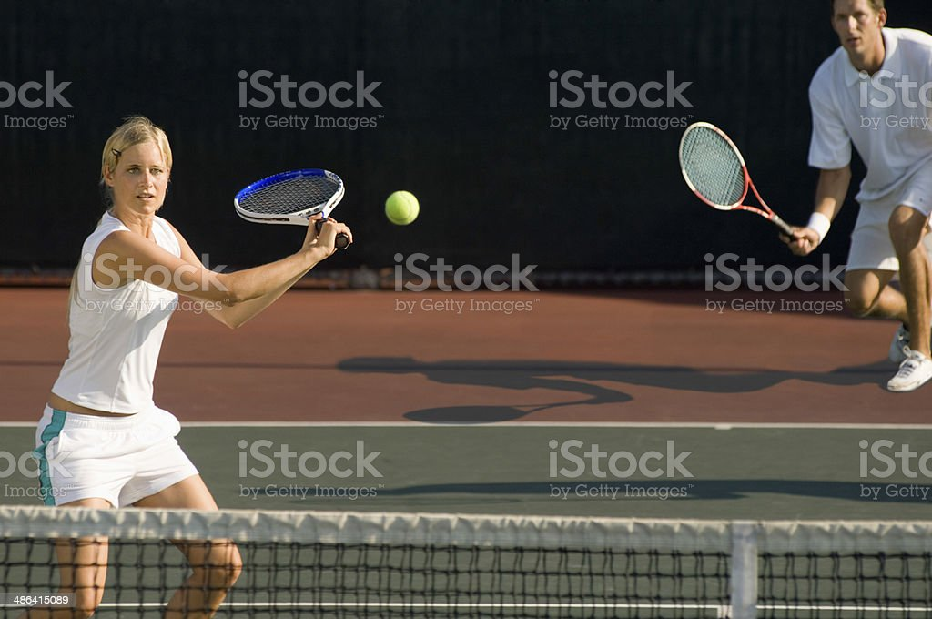 Tennis Player Hitting Ball With Partner Standing In Background stock photo