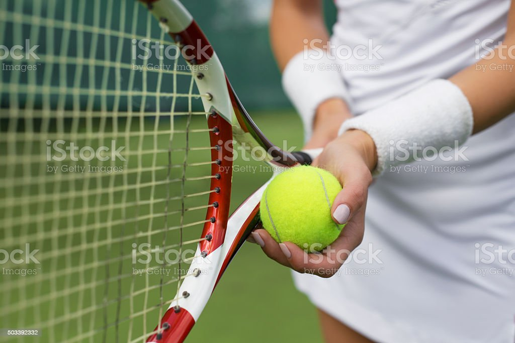 Tennis player holding racket and ball in hands stock photo