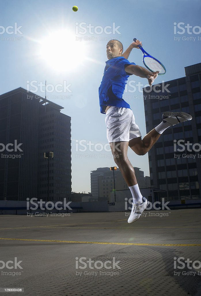 Tennis player jumping on rooftop court stock photo