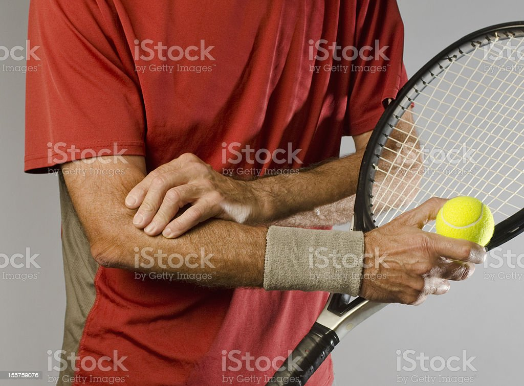 tennis player massaging elbow stock photo