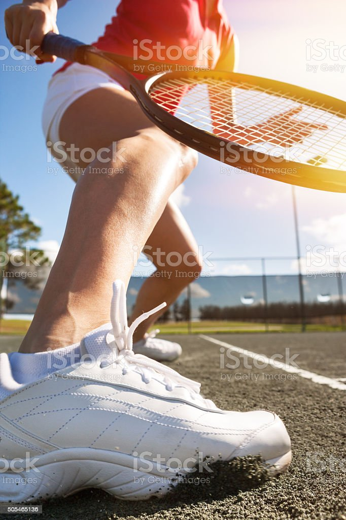 Tennis player sliding into forehand on har-tru tennis court stock photo