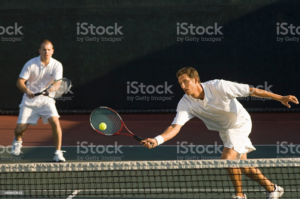 Tennis Player Swinging at Ball stock photo