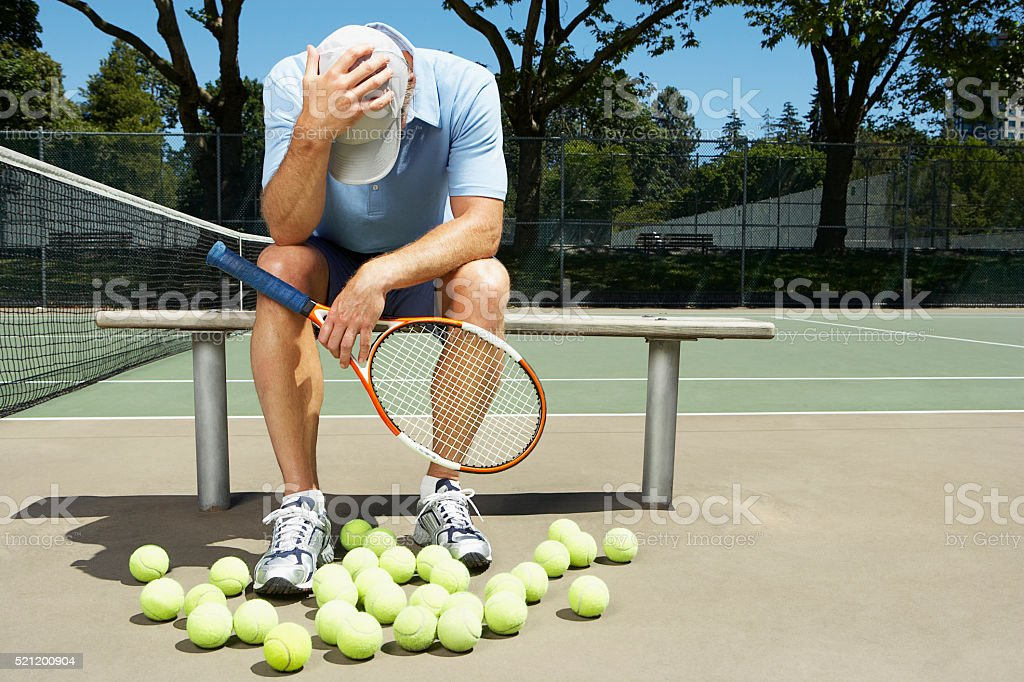 Tennis player with his head in his hands stock photo