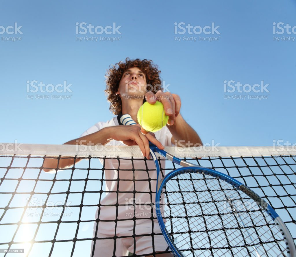 tennis player with racket and ball standing in front of the net stock photo