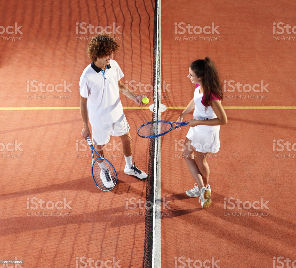 tennis players with racket and ball standing in front of the net stock photo