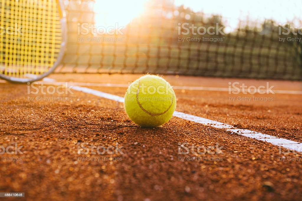 Tennis racket and ball on a clay court stock photo