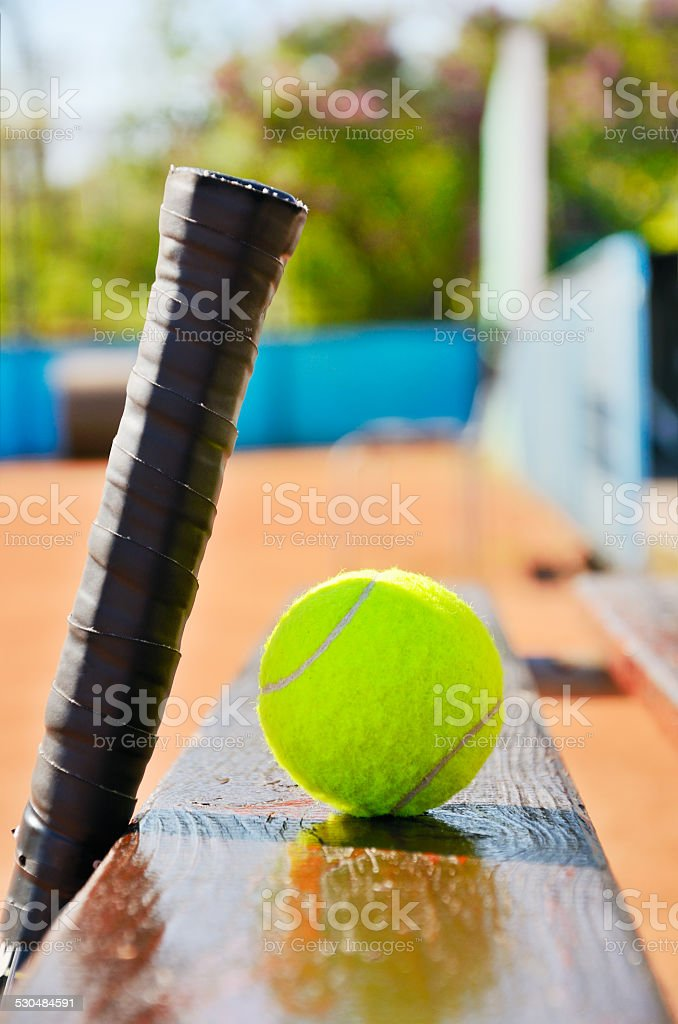 tennis racket and ball on the bench at court stock photo
