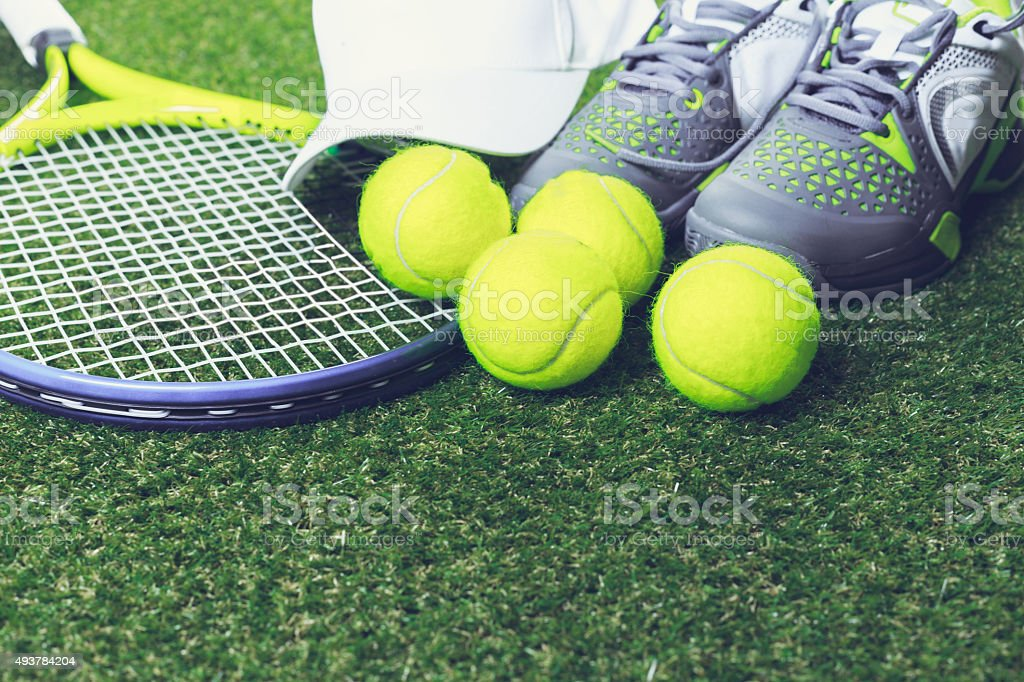 tennis racket and new tennis ball on green court stock photo