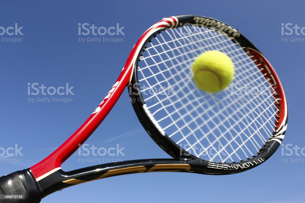 Tennis racket hitting the ball stock photo