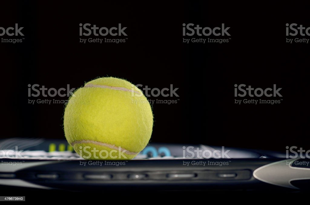 Tennis racket isolated on black background with tennis ball stock photo