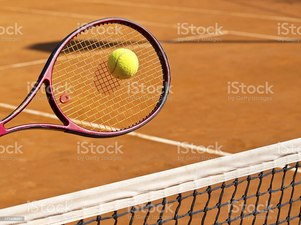Tennis racquet hitting tennis ball over net at clay court royalty-free stock photo