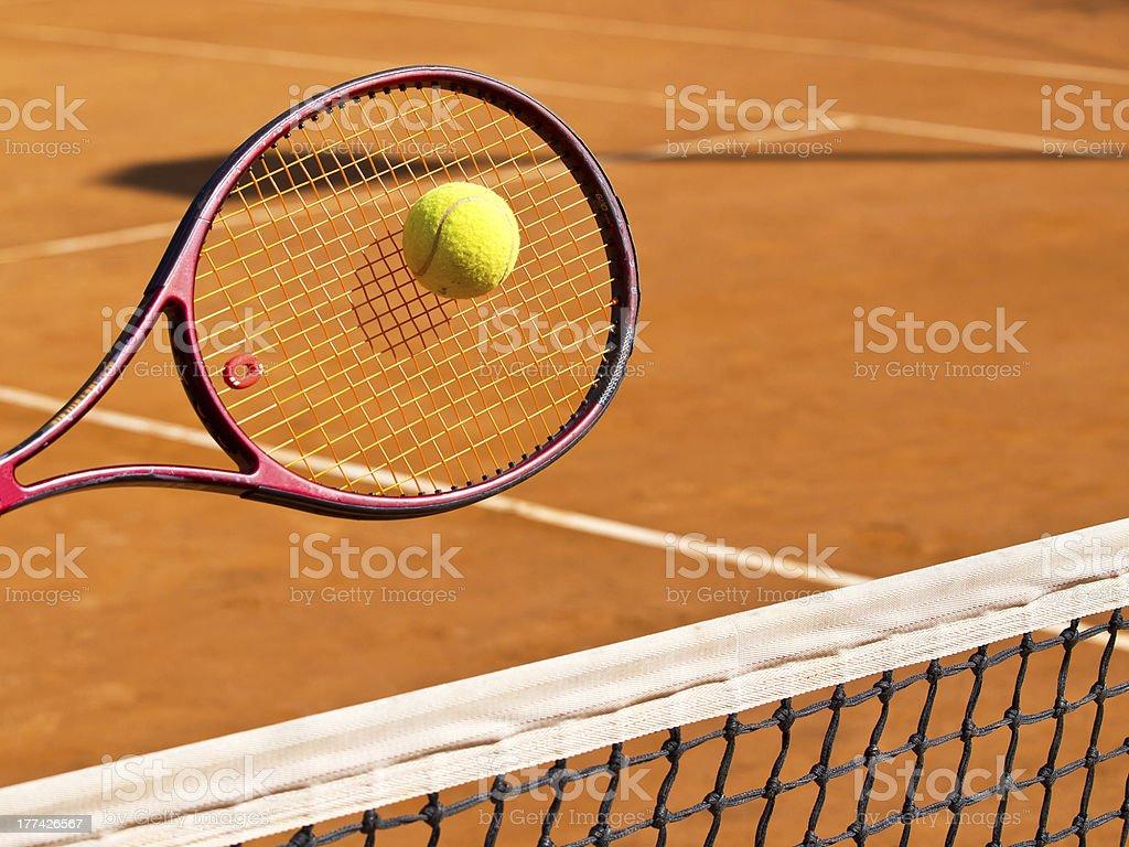 Tennis racquet hitting tennis ball over net at clay court stock photo