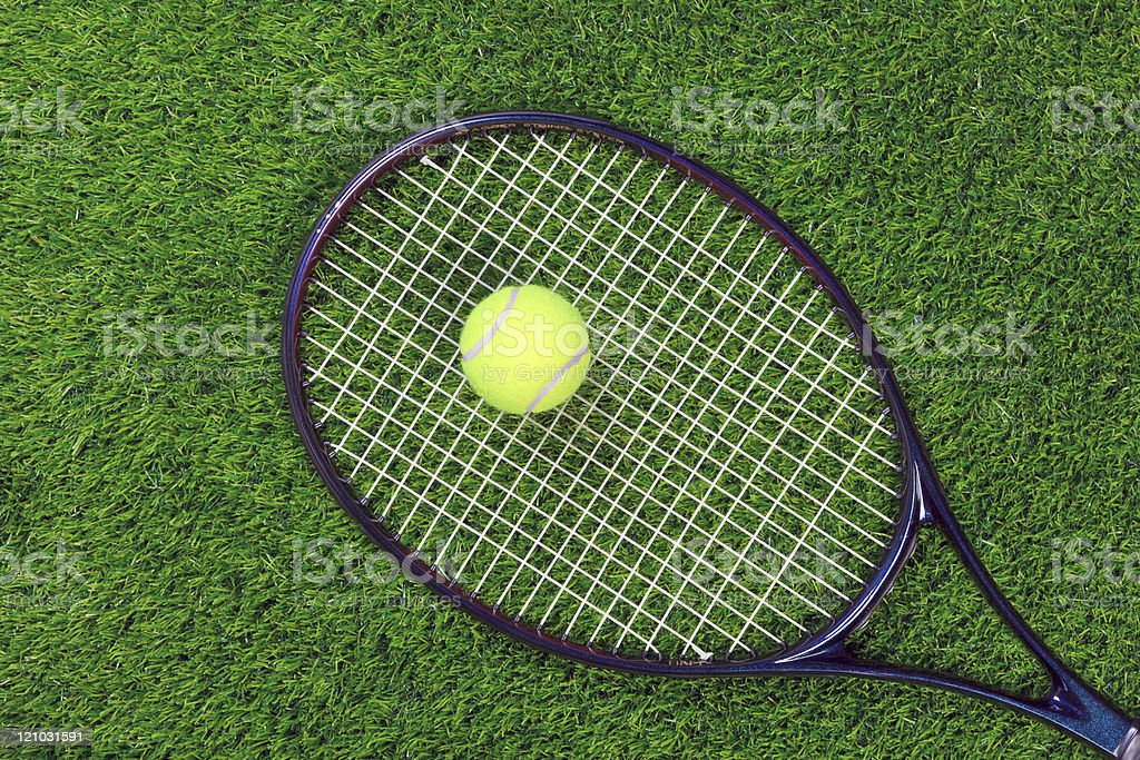 Tennis raquet and ball on grass royalty-free stock photo