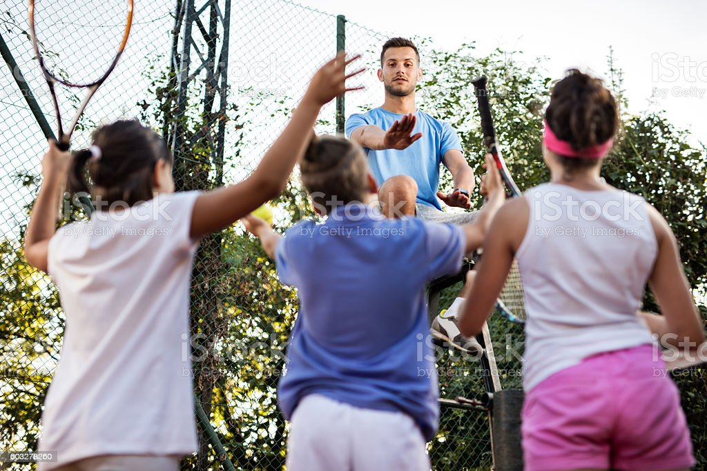Tennis referee arguing with group of children on tennis court. stock photo