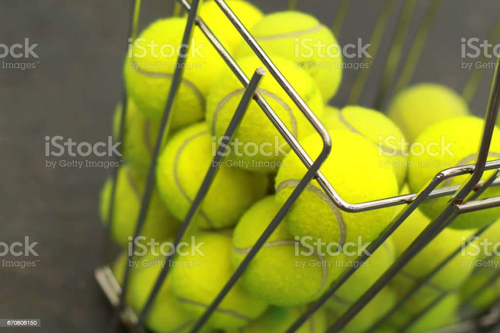 The basket with tennis balls. Ball for plying tennis. Active sport.