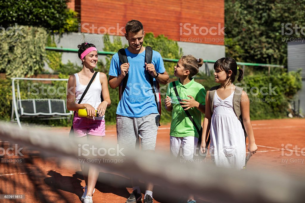 Tennis trainer talking with group of children after training. stock photo