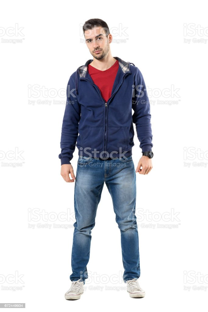 Tense young casual man in blue hooded sweatshirt looking at camera skeptically stock photo