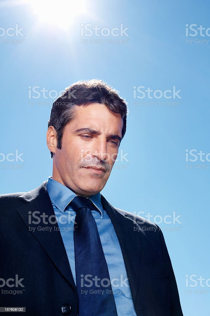 Tensed business man against clear blue sky royalty-free stock photo