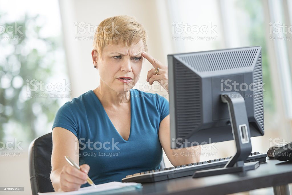 Tensed Businesswoman Working On Desktop PC royalty-free stock photo