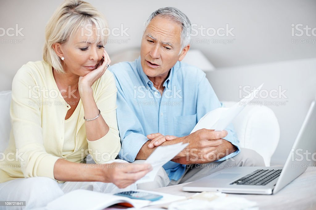 Tensed mature couple discussing their monthly expenses at home royalty-free stock photo