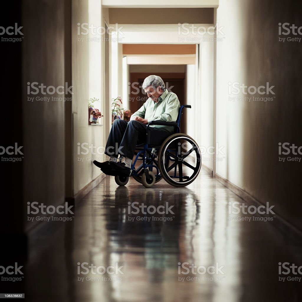Tensed old man sitting on a wheelchair in hospital corridor royalty-free stock photo