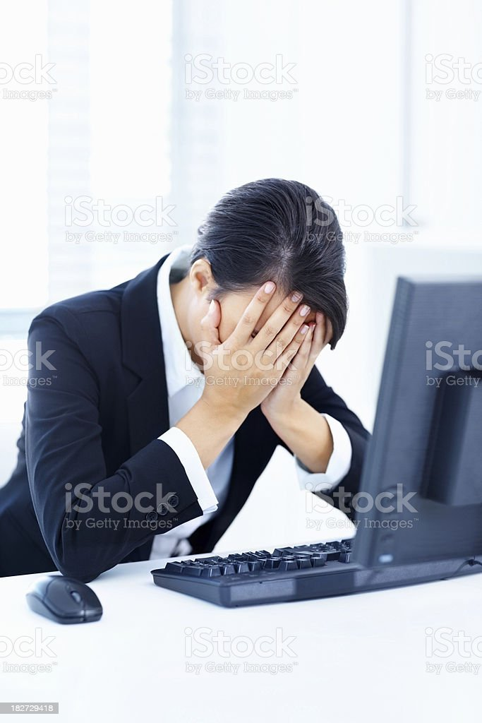 Tensed woman with head in hands at work royalty-free stock photo