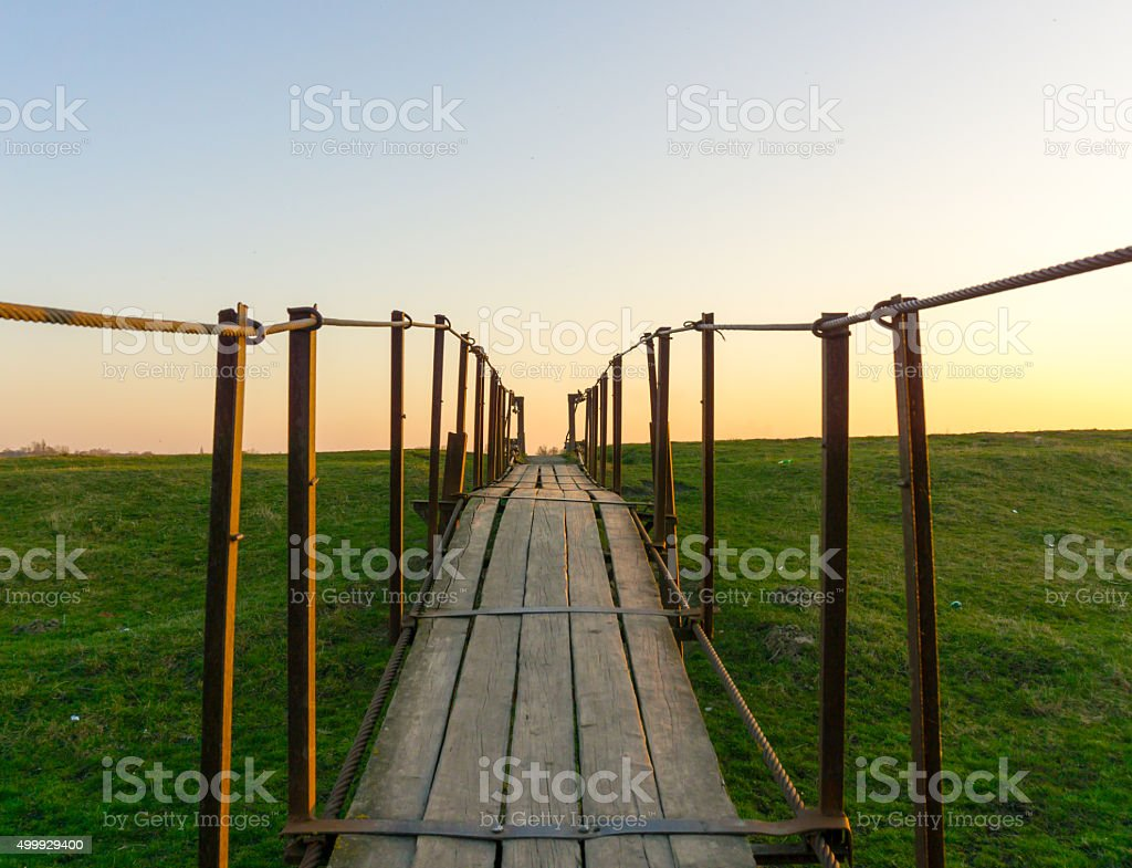 Tension bridge stretching into sunset filtered stock photo