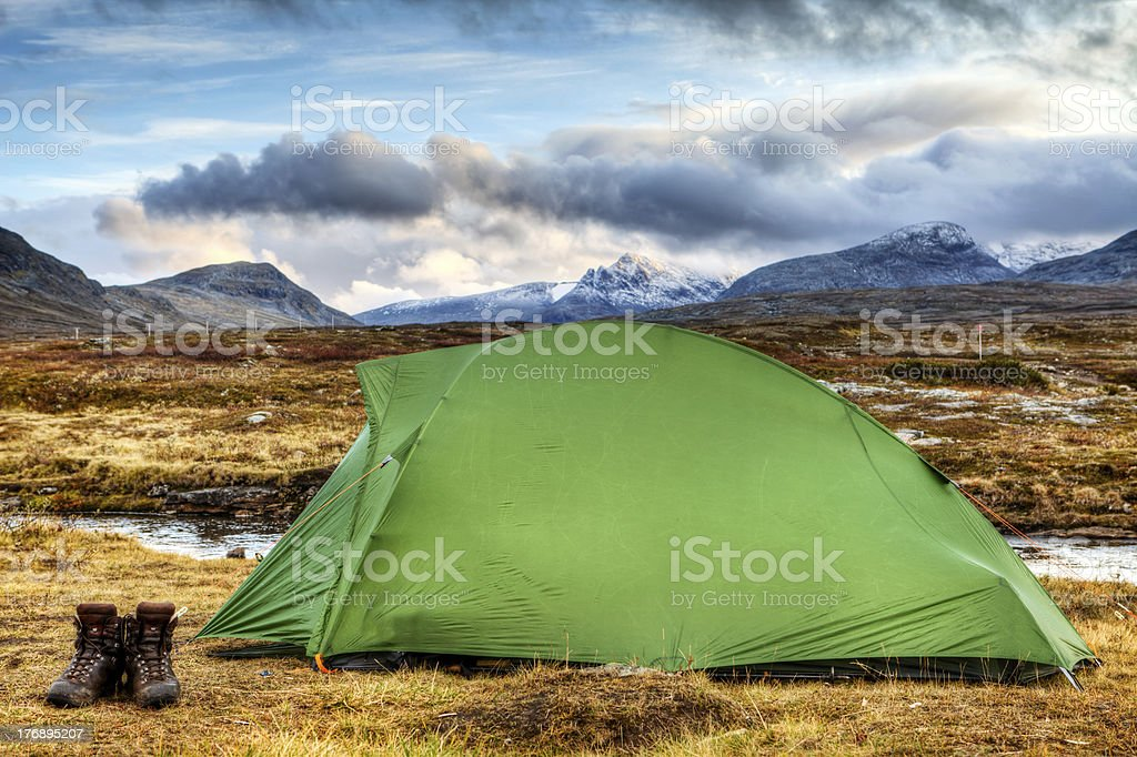 Tent and Hiking boots in autumn royalty-free stock photo