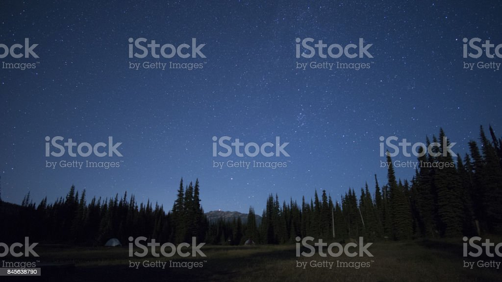 Starry summer night over a hiking campground and mountain scenery.