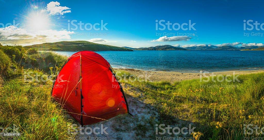 Tent camping on summer sand dunes beside island ocean beach stock photo