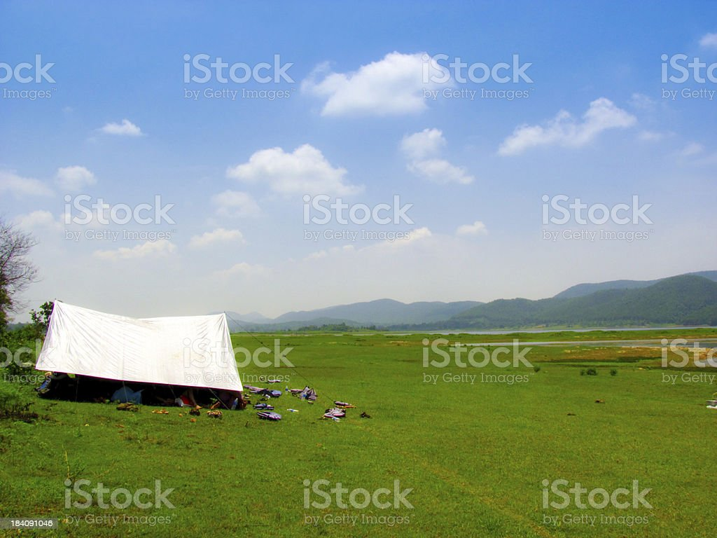 tent in a green feild bordered by hills royalty-free stock photo