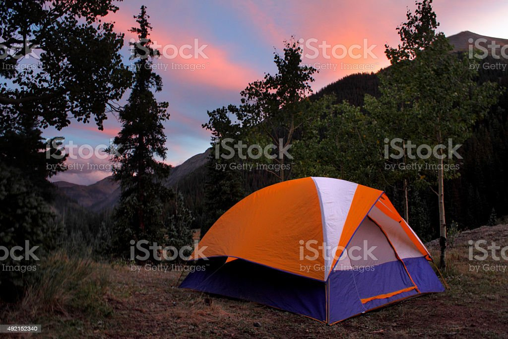 Tent in the woods at sunset stock photo