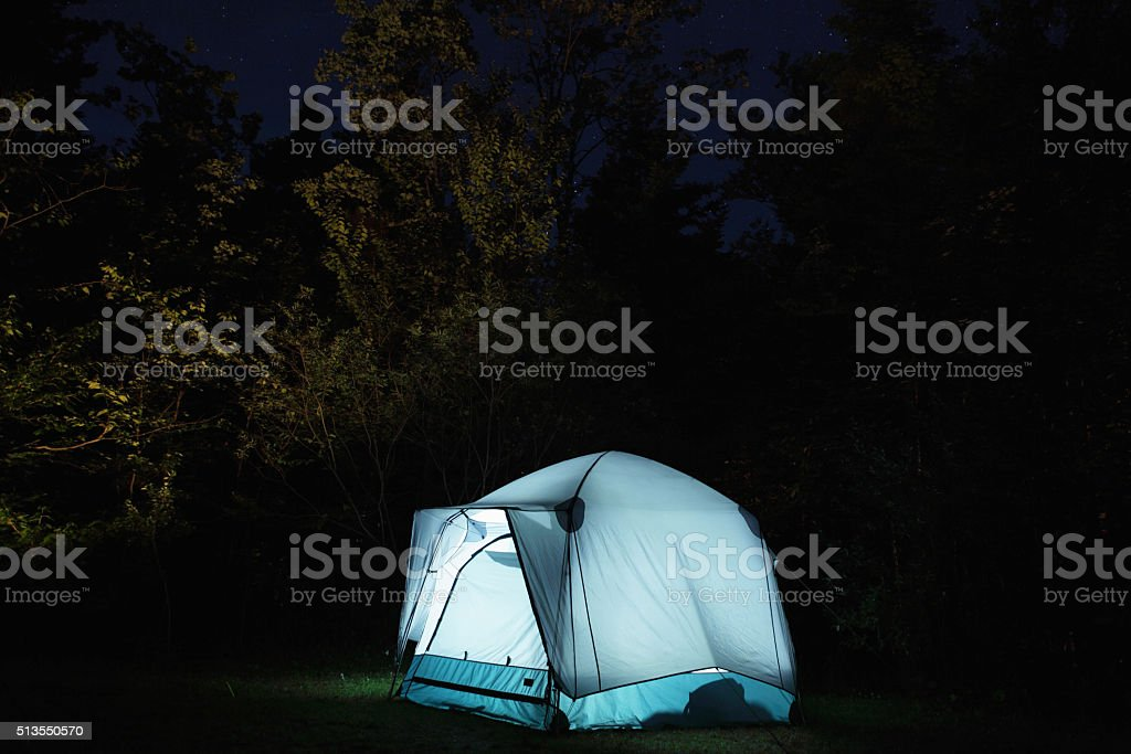 Tent lit up at night under starry sky stock photo
