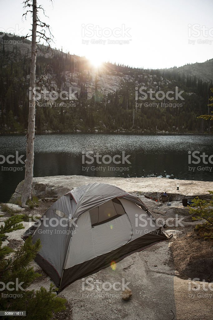 Tent pitched alongside a mountain lake at sunset royalty-free stock photo