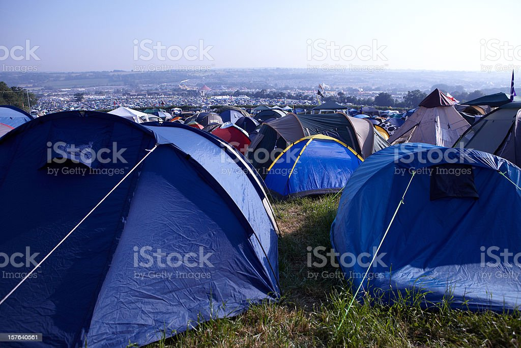 Tents crowded together on a grassy hill for a festival stock photo